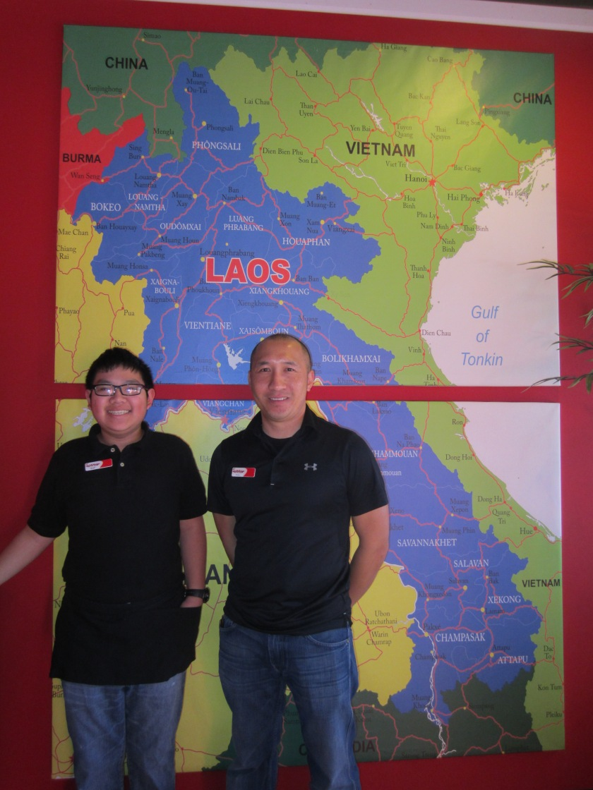 Eric stands in front of a large canvas map of Laos with his nephew, Noah, who also works at the restaurant. Many customers who come in end up taking pictures with the map. Eric says that the map serves to educate people about Laos.
